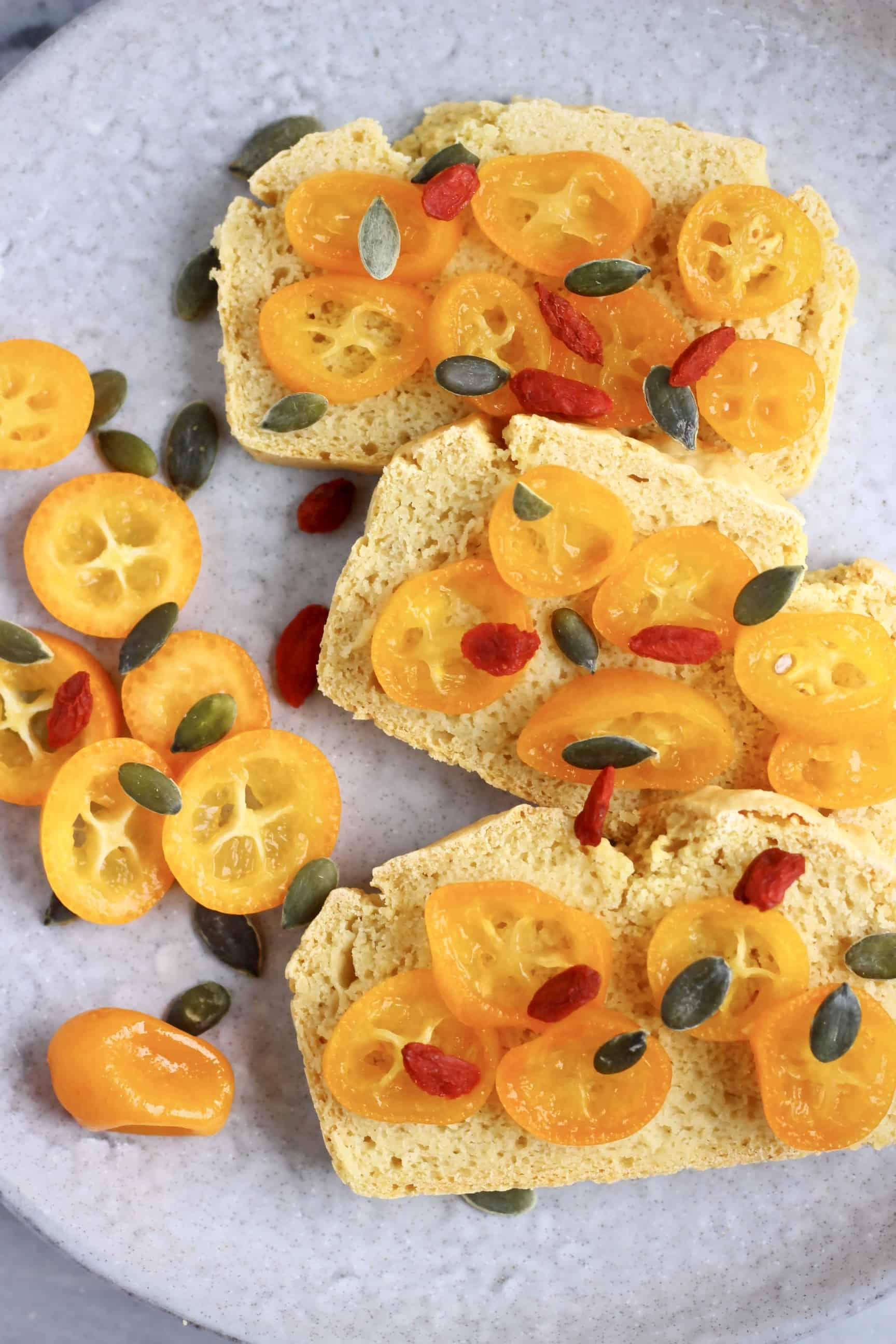 Three slices of gluten-free vegan bread topped with sliced kumquats, goji berries and pumpkin seeds on a grey plate