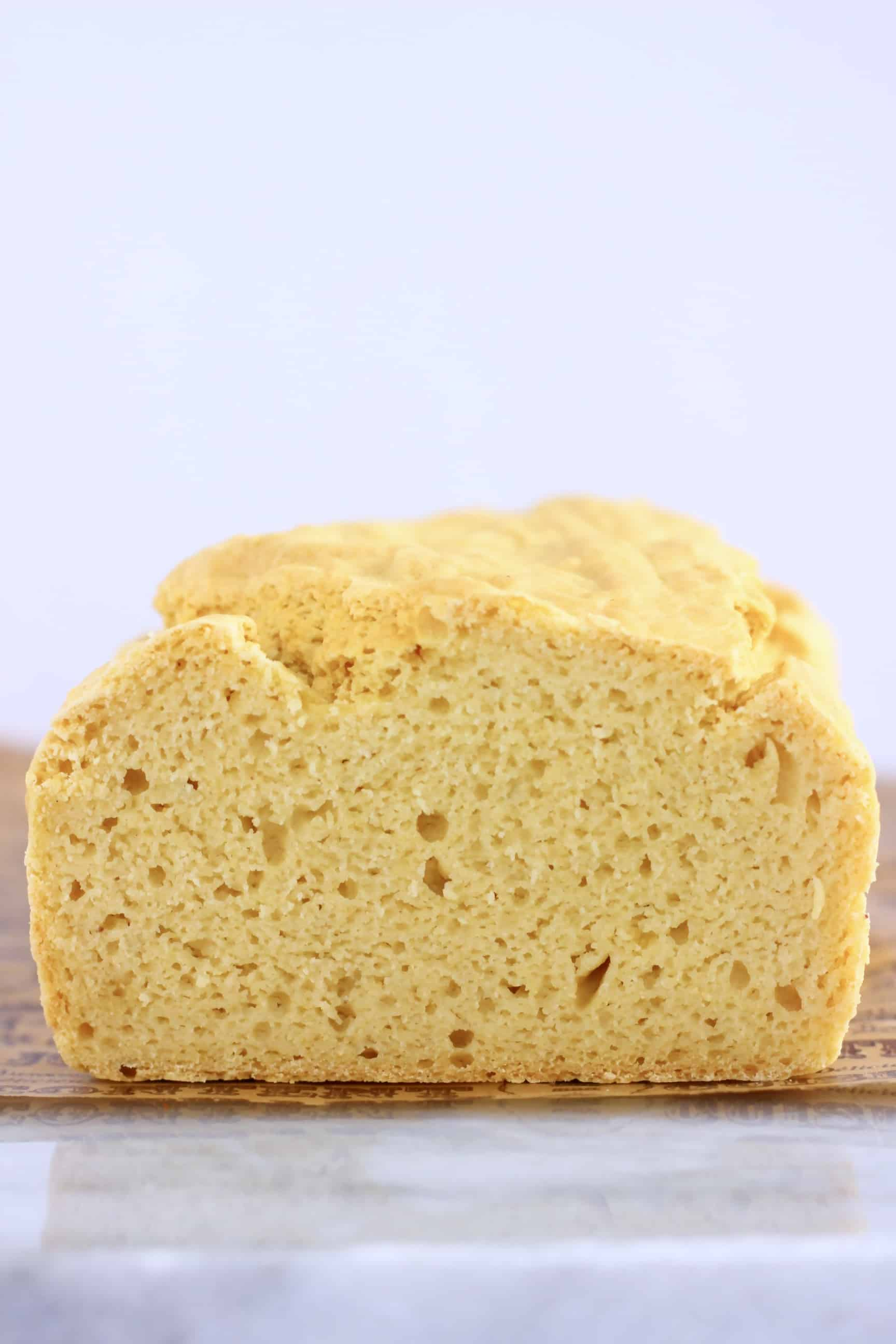 A cross-section of a loaf of gluten-free vegan bread on a marble slab