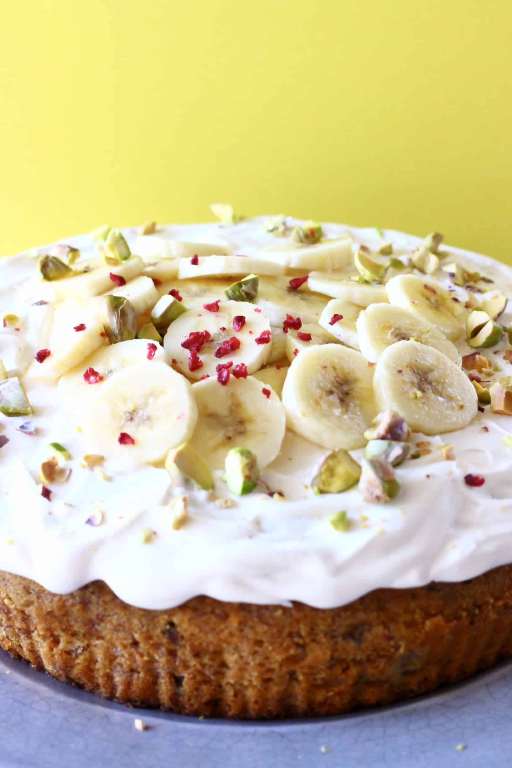 A gluten-free vegan banana cake topped with vegan cream cheese  frosting and sliced bananas