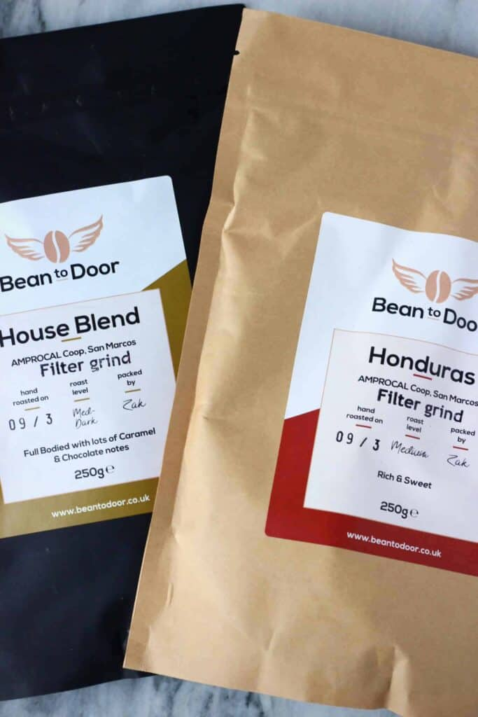 Photo of a beige packet of Bean to Door coffee and a black packet of Bean to Door coffee on a marble background
