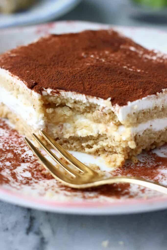 Photo of a slice of tiramisu with a bite taken out of it on a white plate with pink flowers and a gold fork