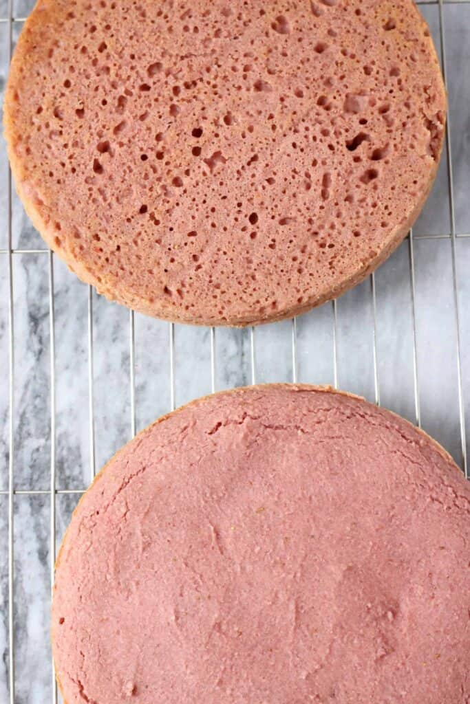 Two round pink strawberry cake sponges on a wire rack