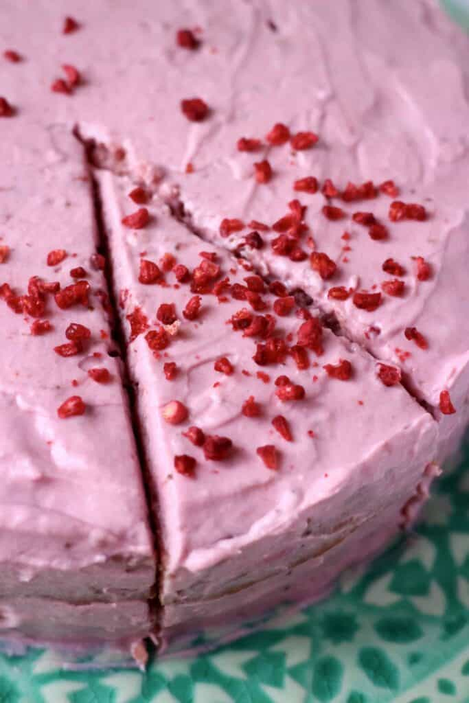 A pink strawberry sponge layer cake with pink strawberry frosting with a slice cut