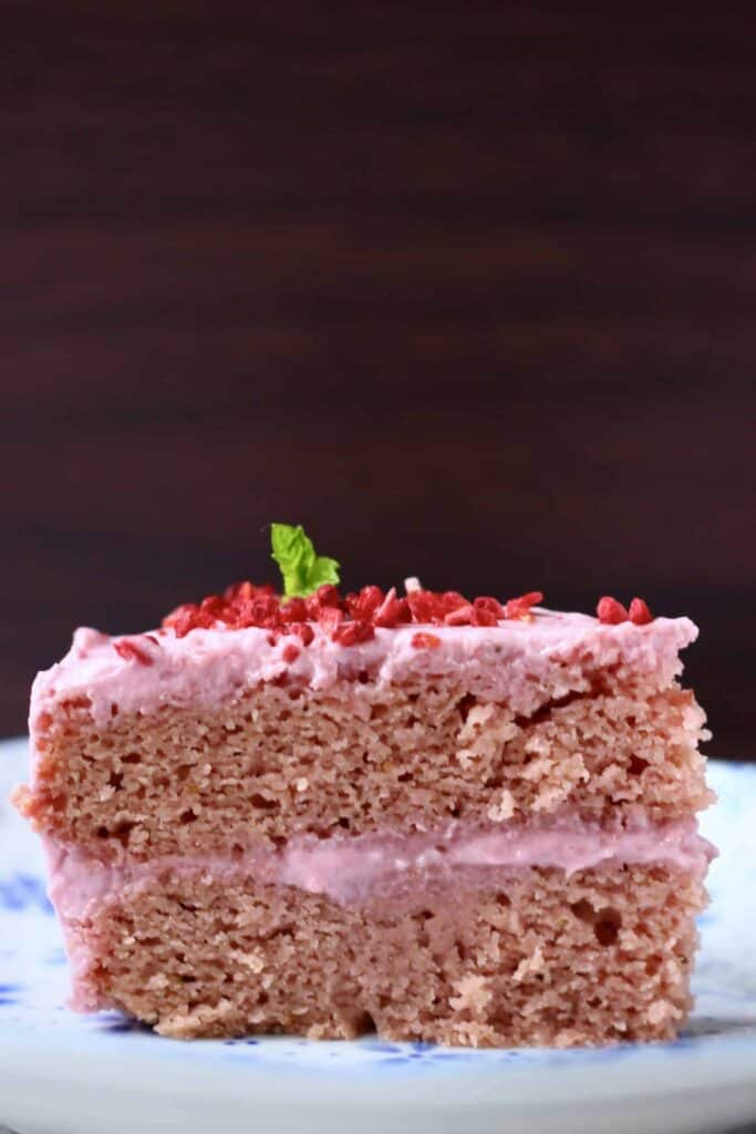 A slice of pink strawberry sponge layer cake with pink strawberry frosting