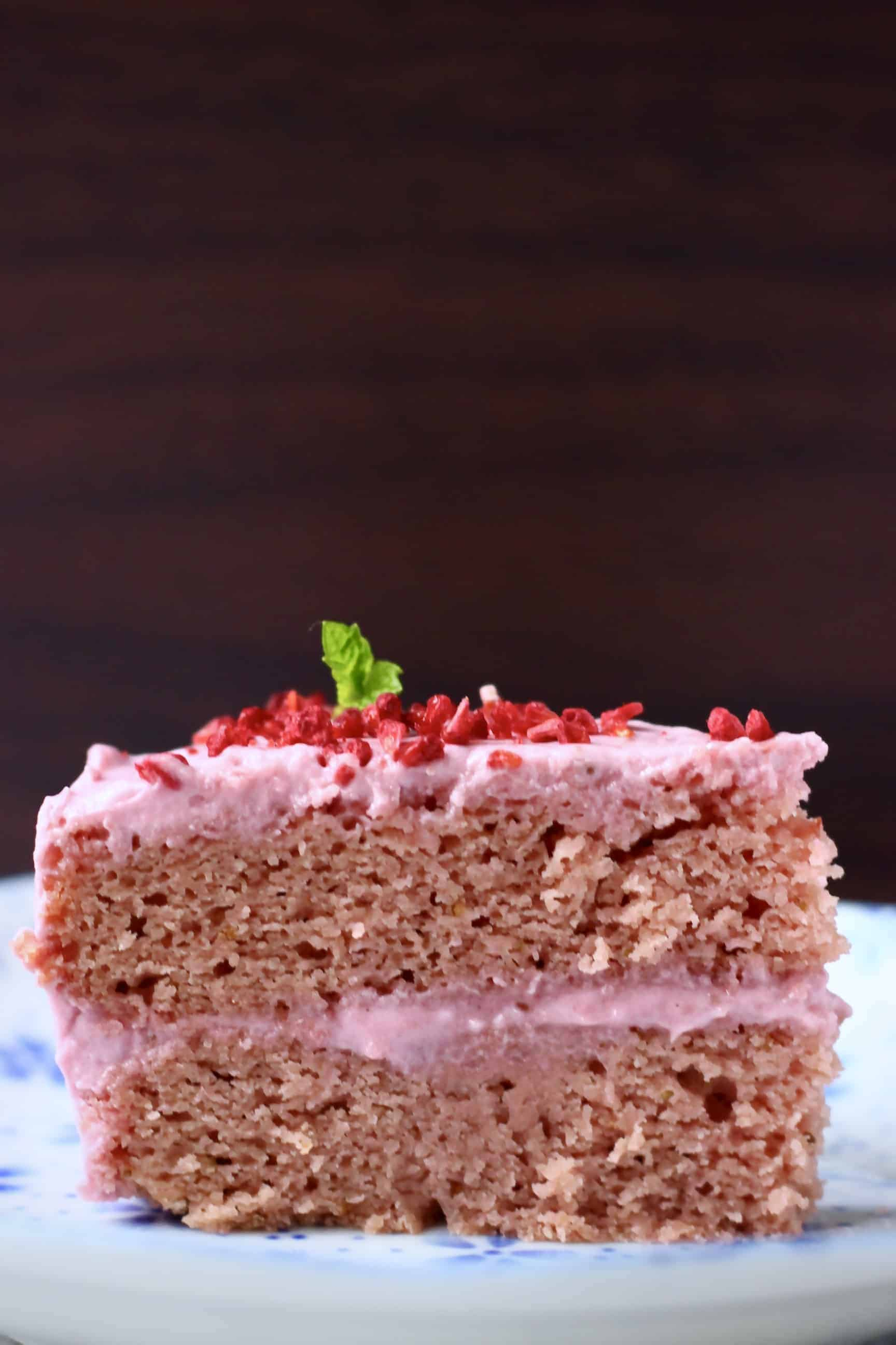 A slice of pink gluten-free vegan strawberry cake with pink strawberry frosting