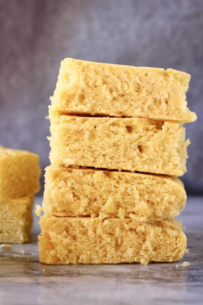 Photo of four squares of cornbread stacked on top of each other on a marble slab against a grey background