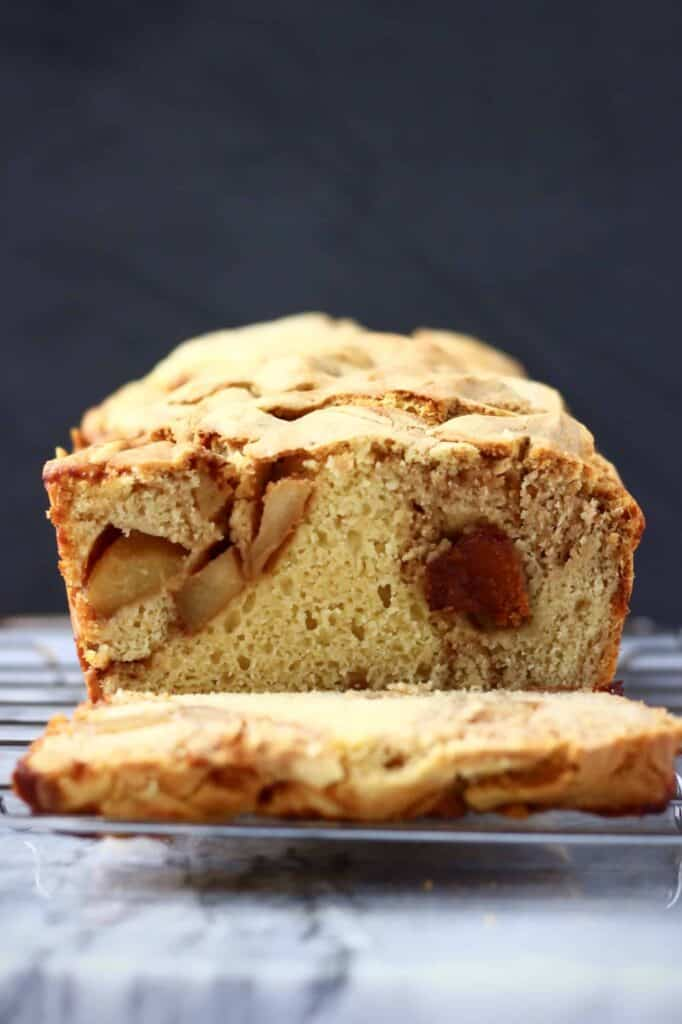 Photo of a sliced loaf of apple bread on a silver wire rack on a marble slab against a black background