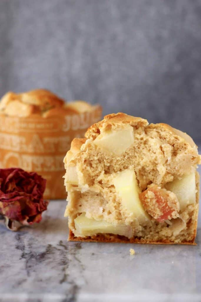 Photo of half a muffin with apples and another muffin on a marble slab against a grey background