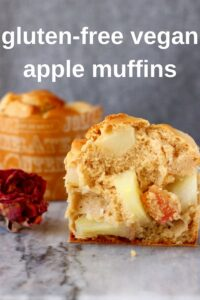 Two apple muffins on a marble board with a grey background, one cut in half