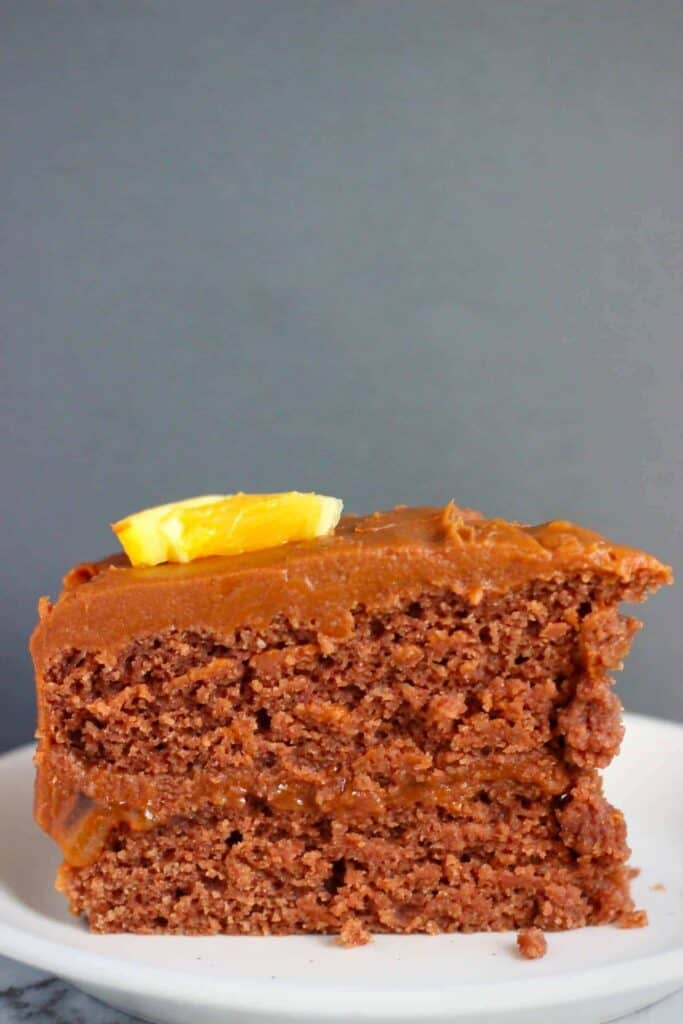 Photo of a slice of chocolate cake topped with an orange wedge on a white plate against a grey background