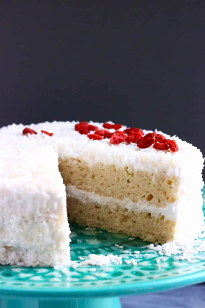 Photo of a sliced sponge cake frosted with creamy white frosting, coated in coconut and topped with red goji berries on a green cake stand against a dark grey background