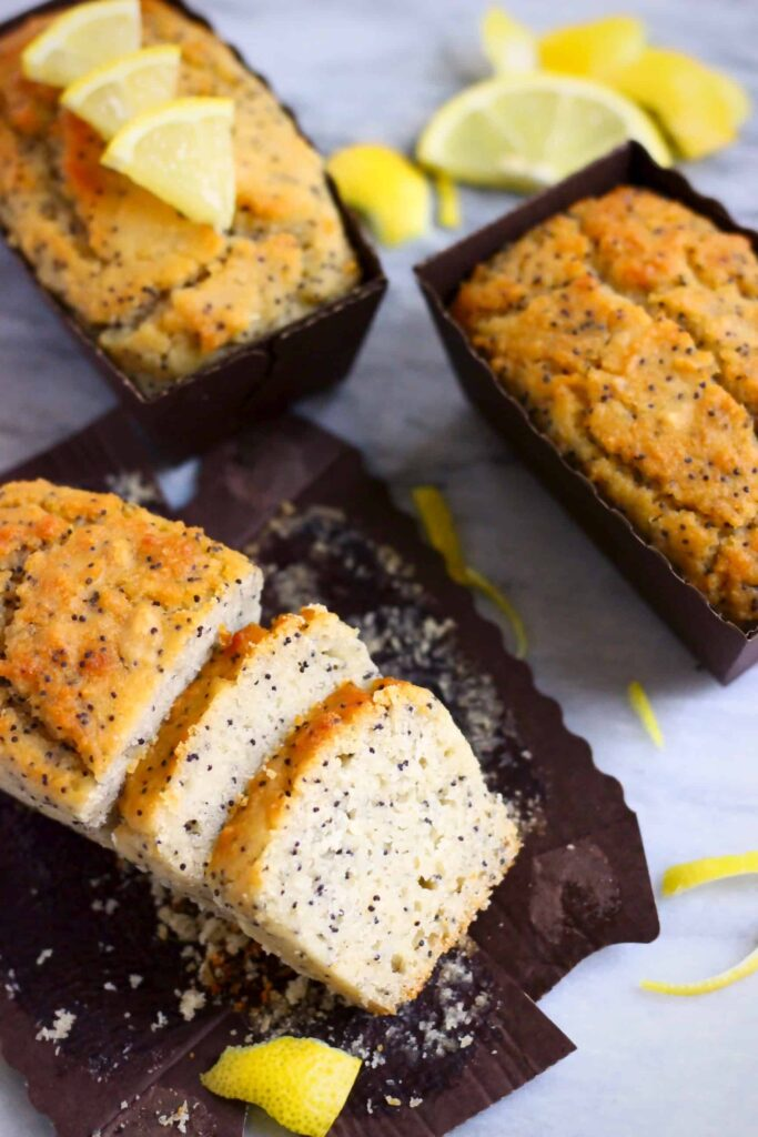 Three lemon poppy seed loaf cakes against a marble background, one sliced