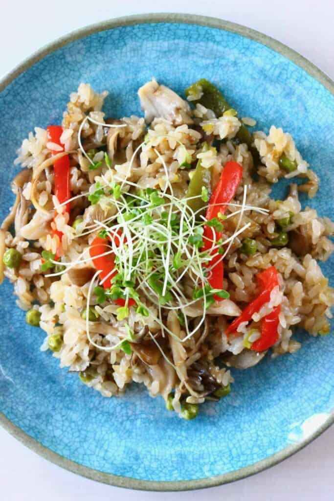 Rice with mushrooms and red peppers with cress on a blue plate against a white background