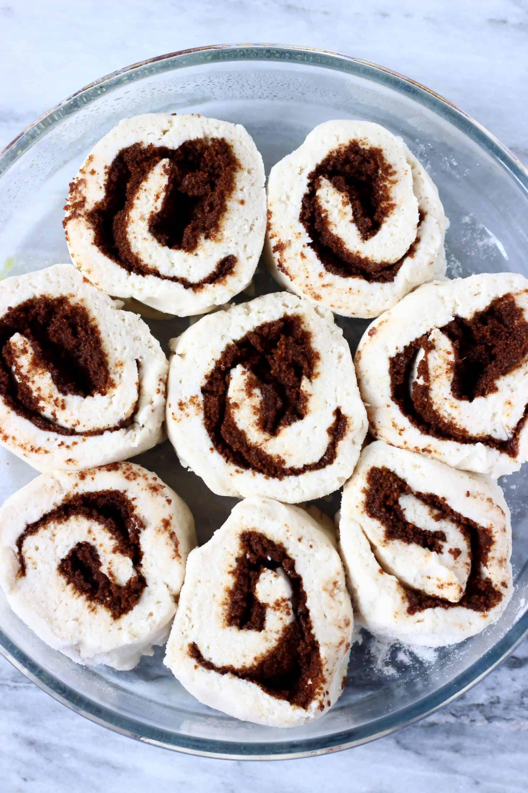 Eight raw gluten-free vegan cinnamon rolls in a round baking dish before proving