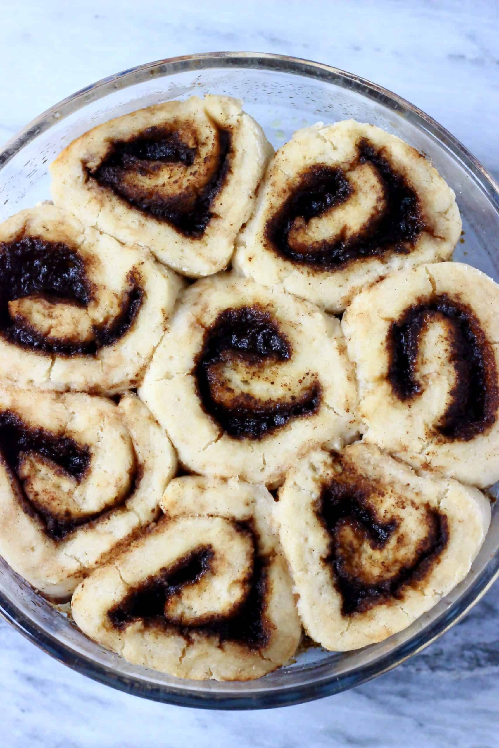 Eight gluten-free vegan cinnamon rolls in a round baking dish