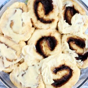 Seven gluten-free vegan cinnamon rolls in a round baking dish, topped with vegan cream cheese frosting