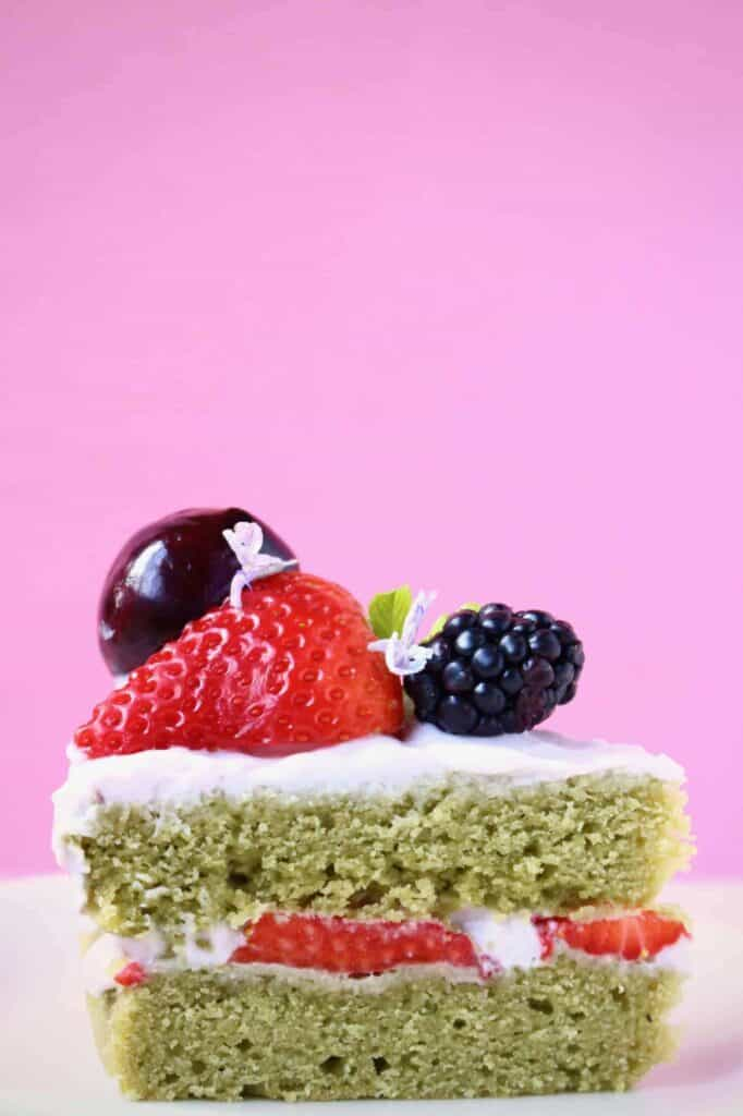Photo of a green sponge cake sandwiched with white creamy frosting and topped with fresh berries against a pink background