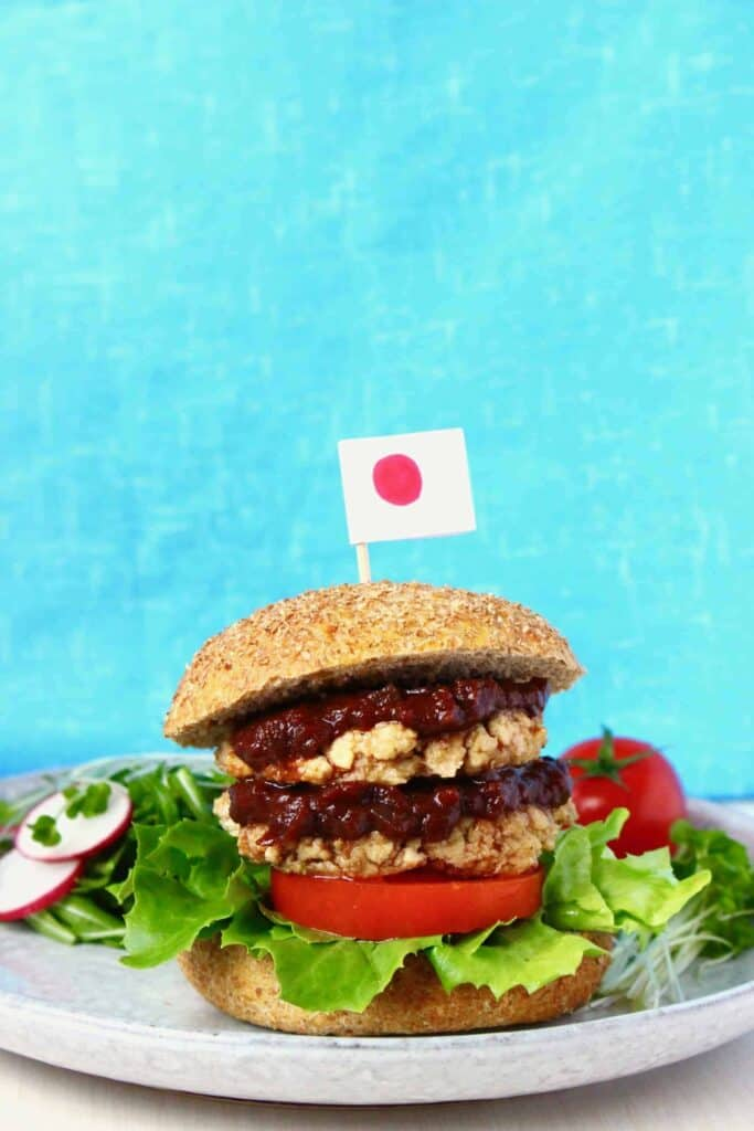 A tofu burger with brown sauce, tomato and lettuce on a grey plate with a Japanese flag on a toothpick sticking out of it against a bright blue background