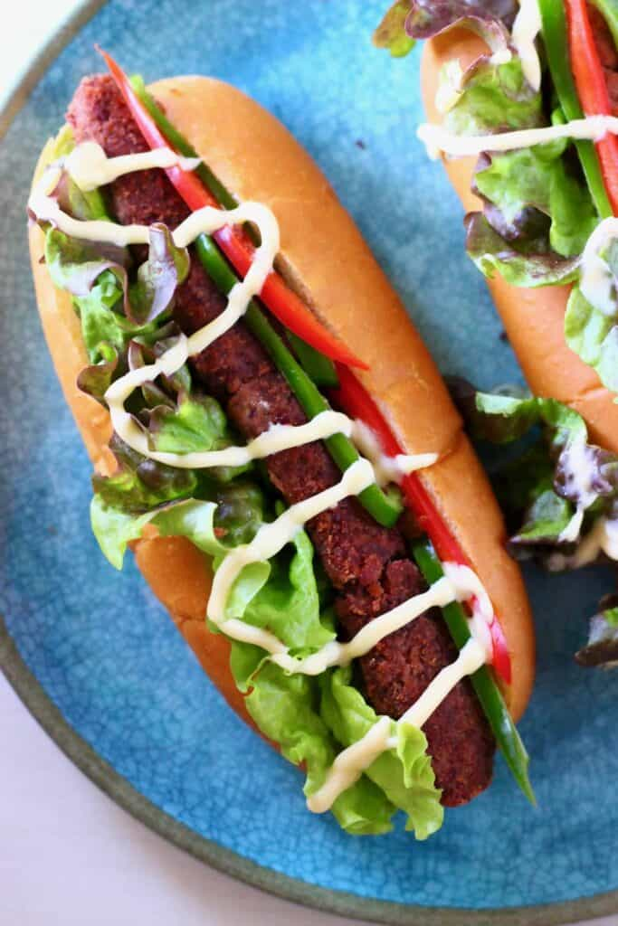 A hot dog with lettuce and sliced red peppers drizzled with mayonnaise on a blue plate