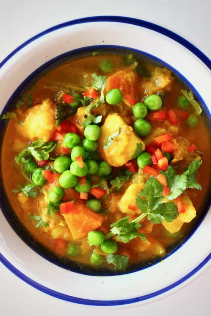 Diced potatoes and green peas in a red curry sauce in a white bowl with a dark blue rim against a white background