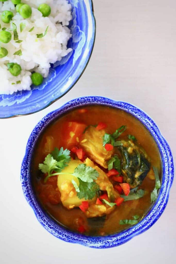 Potatoes in a red curry sauce in a small blue bowl next to another blue bowl with rice and green peas against a white background
