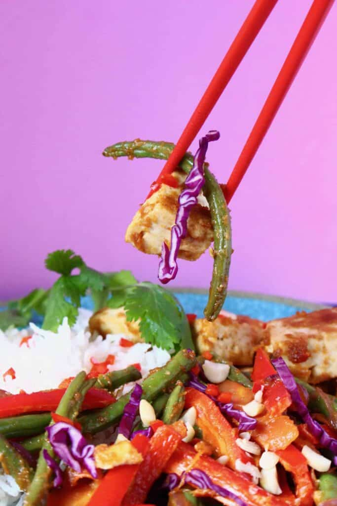 A tofu and vegetable stir fry on a plate with a pair of red chopsticks holding up a mouthful against a pink background