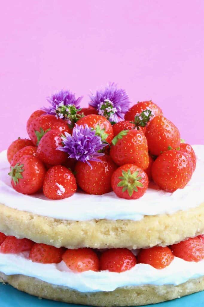 Photo of a sponge cake frosted with white creamy frosting topped with a pile of tiny strawberries and purple flowers against a pink background