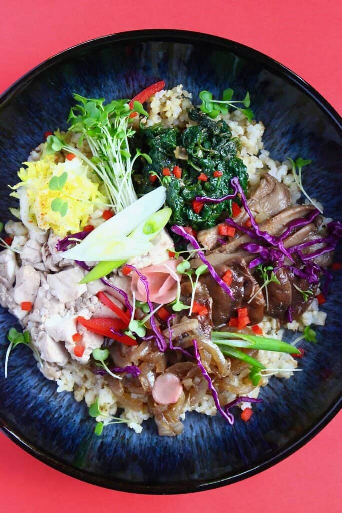 Scrambled tofu, oyster mushrooms, spinach, green cress and other vegetables on a bed of rice in a dark blue bowl against a red background