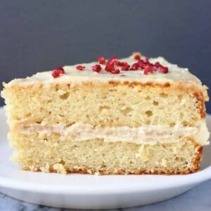 A slice of gluten-free vegan vanilla cake with buttercream on a plate