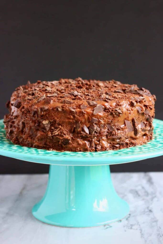 Photo of a chocolate cake covered in bits of chopped up chocolate on a blue cake stand against a grey background