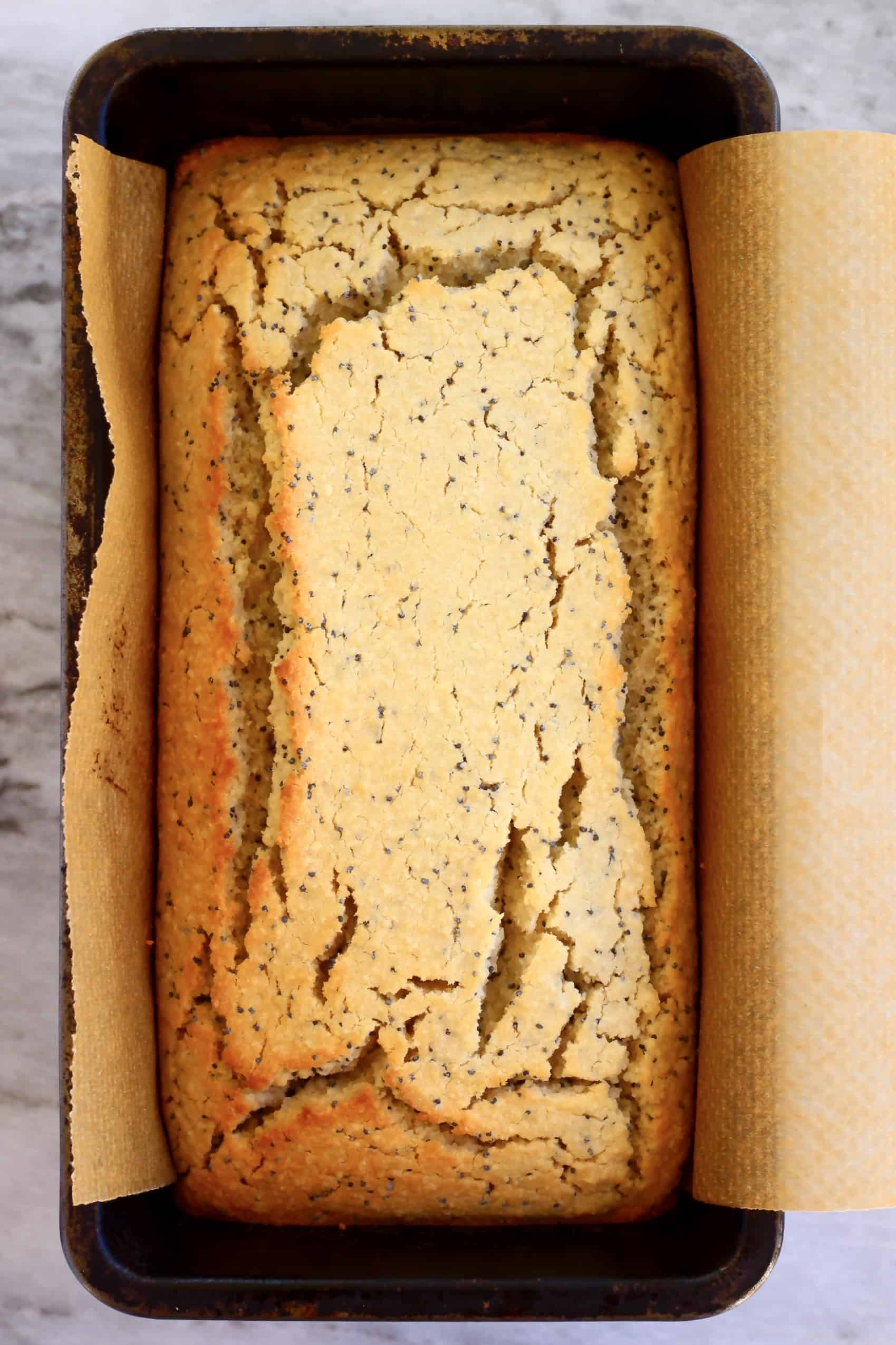 Gluten-free vegan lemon poppy seed cake in a loaf tin lined with baking paper