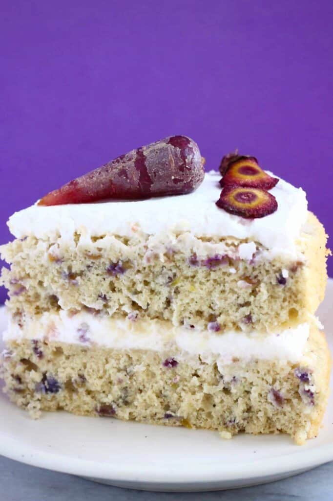 A slice of carrot cake made with purple carrots topped with a purple carrot, on a small white plate against a purple background