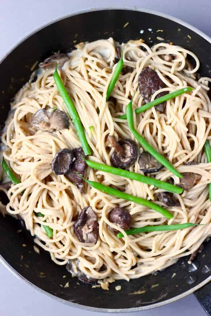 Spaghetti with mushrooms and green beans in a black frying pan against a grey background