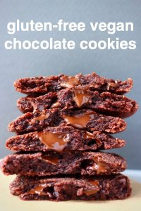 A stack of six chocolate cookies on a sheet of brown baking paper against a grey background