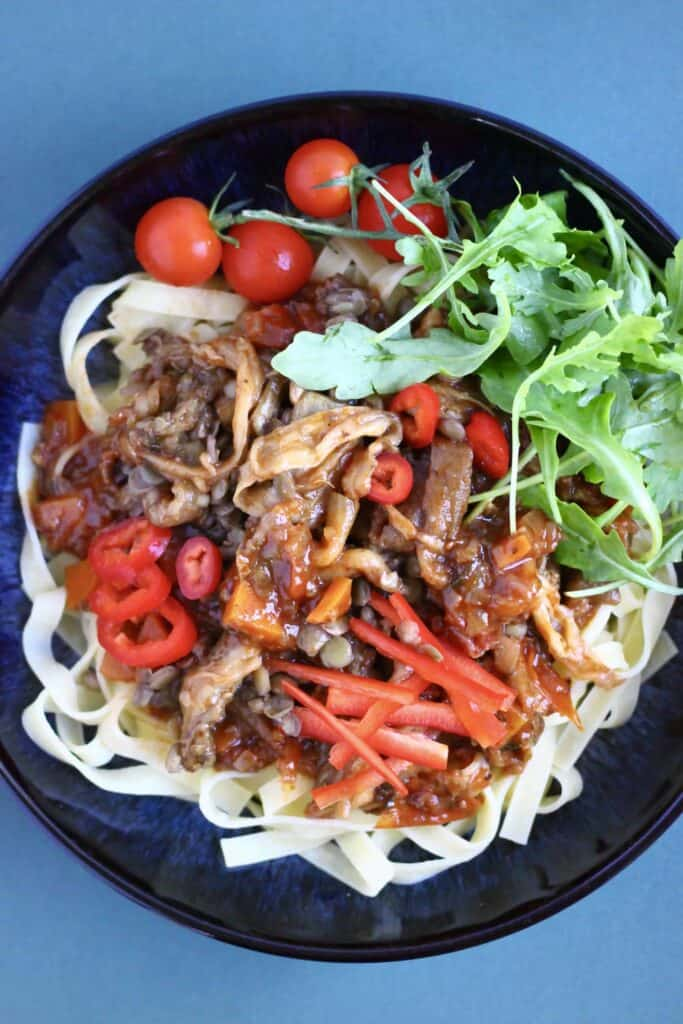 Tagliatelle with shredded eggplant in tomato sauce and rocket in a dark blue bowl against a blue background