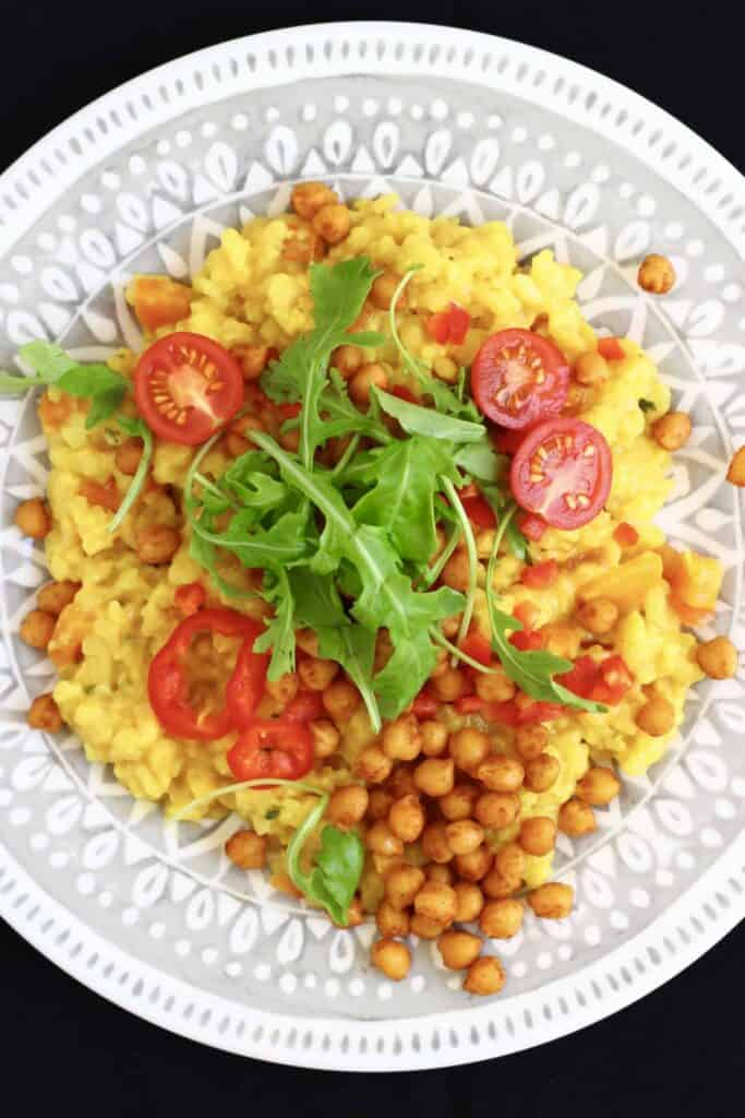 Yellow rice with cherry tomatoes and green rocket with brown chickpeas on a grey plate against a black background
