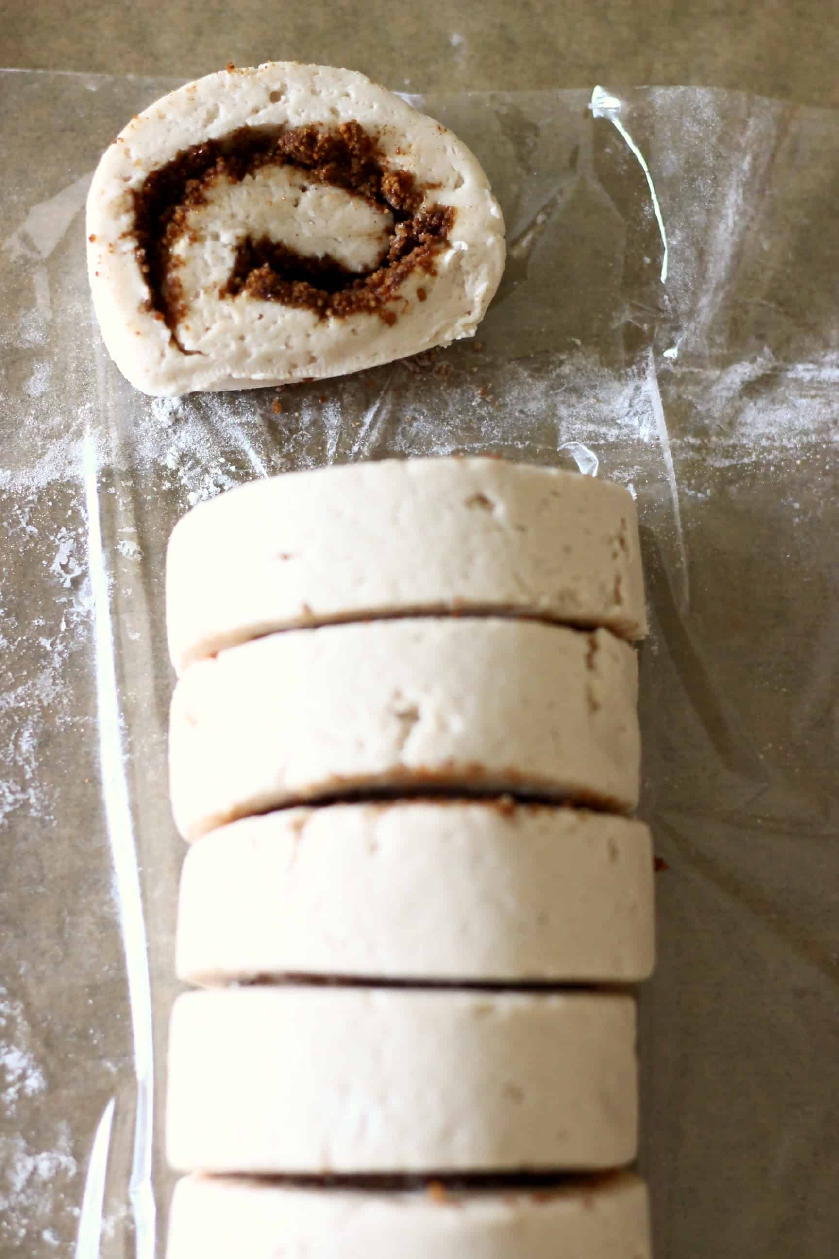 A roll of gluten-free vegan cinnamon roll dough filled with cinnamon sugar being cut into pieces