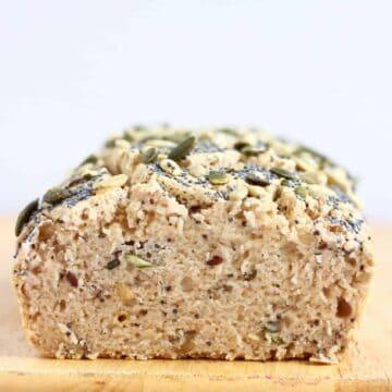 A sliced loaf of Gluten-Free Vegan Seeded Buckwheat Bread on a chopping board