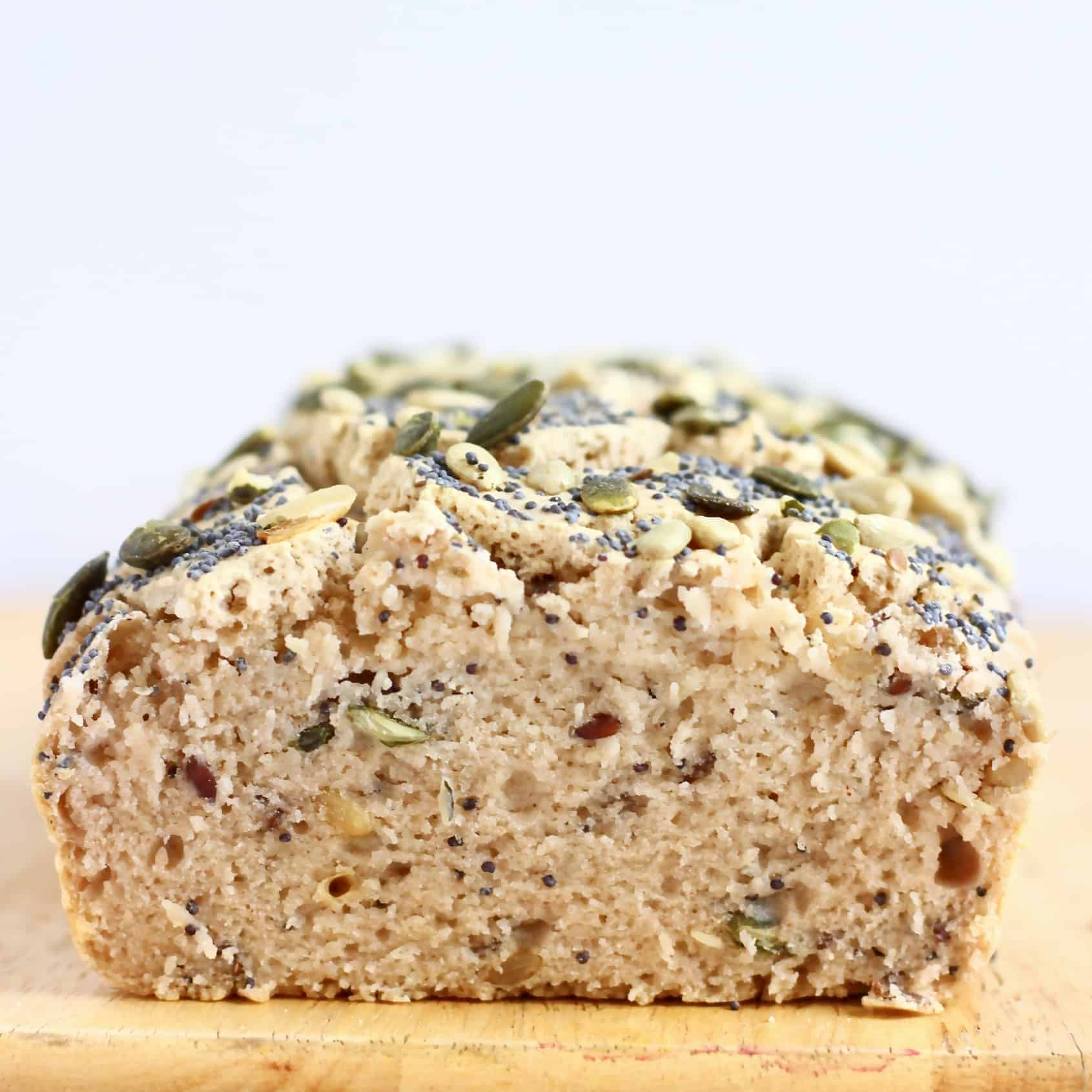 A sliced loaf of Gluten-Free Vegan Seeded Buckwheat Bread on a chopping board