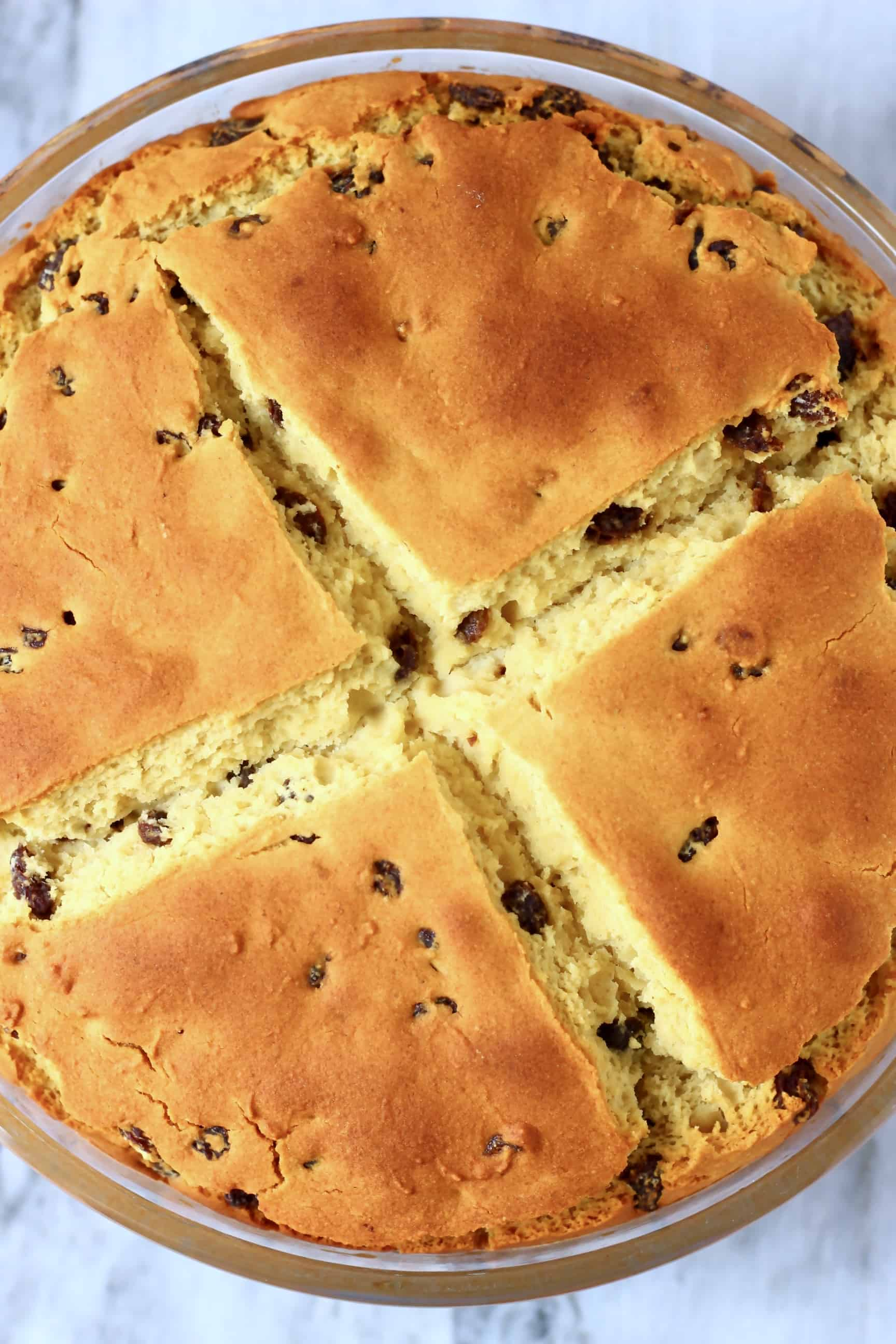 A round loaf of Gluten-Free Vegan Irish Soda Bread with a cross on top in a glass baking dish