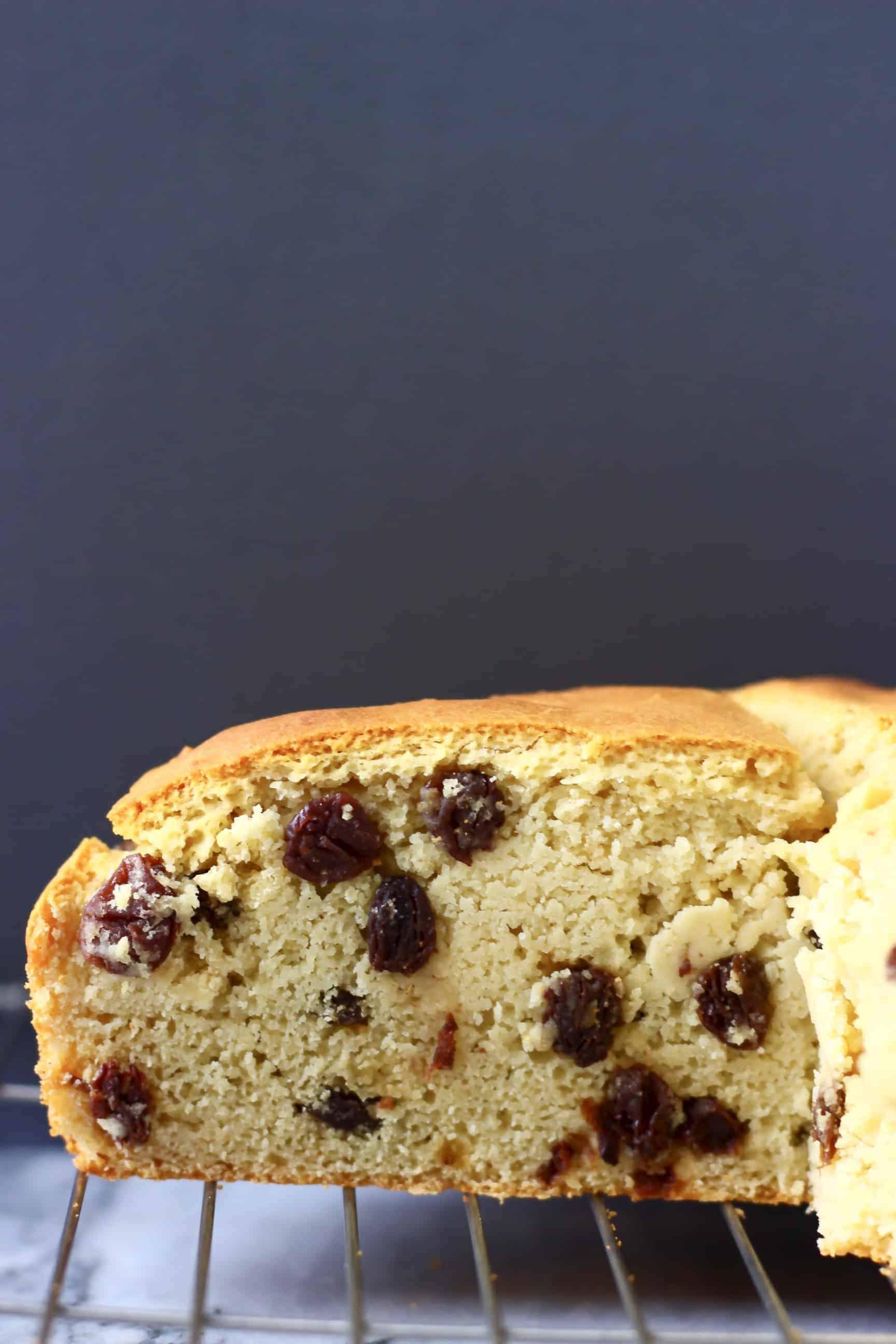 A sliced loaf of Gluten-Free Vegan Irish Soda Bread with raisins on a wire rack