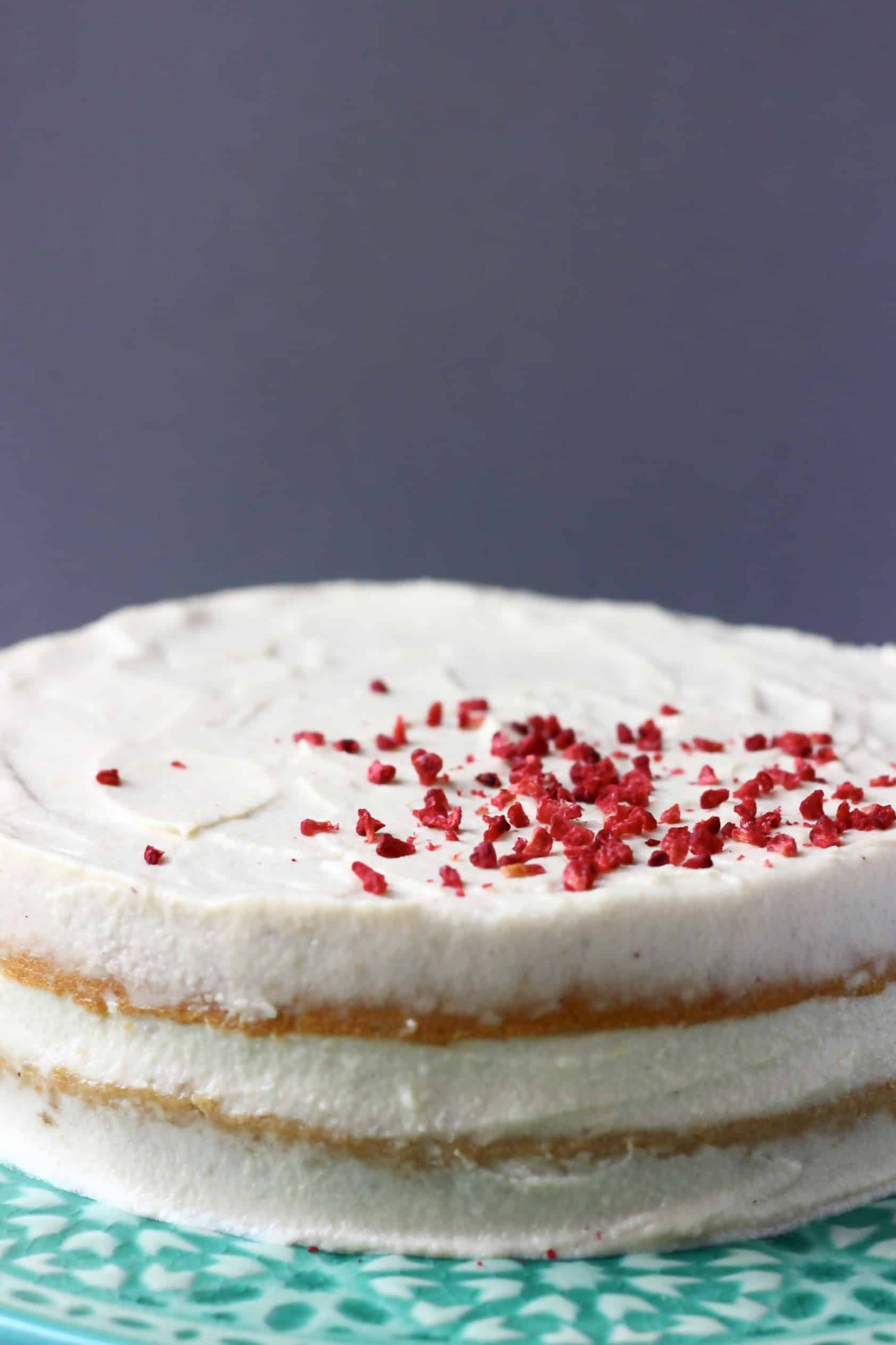 Gluten-free vegan vanilla cake covered with white frosting topped with freeze-dried raspberries