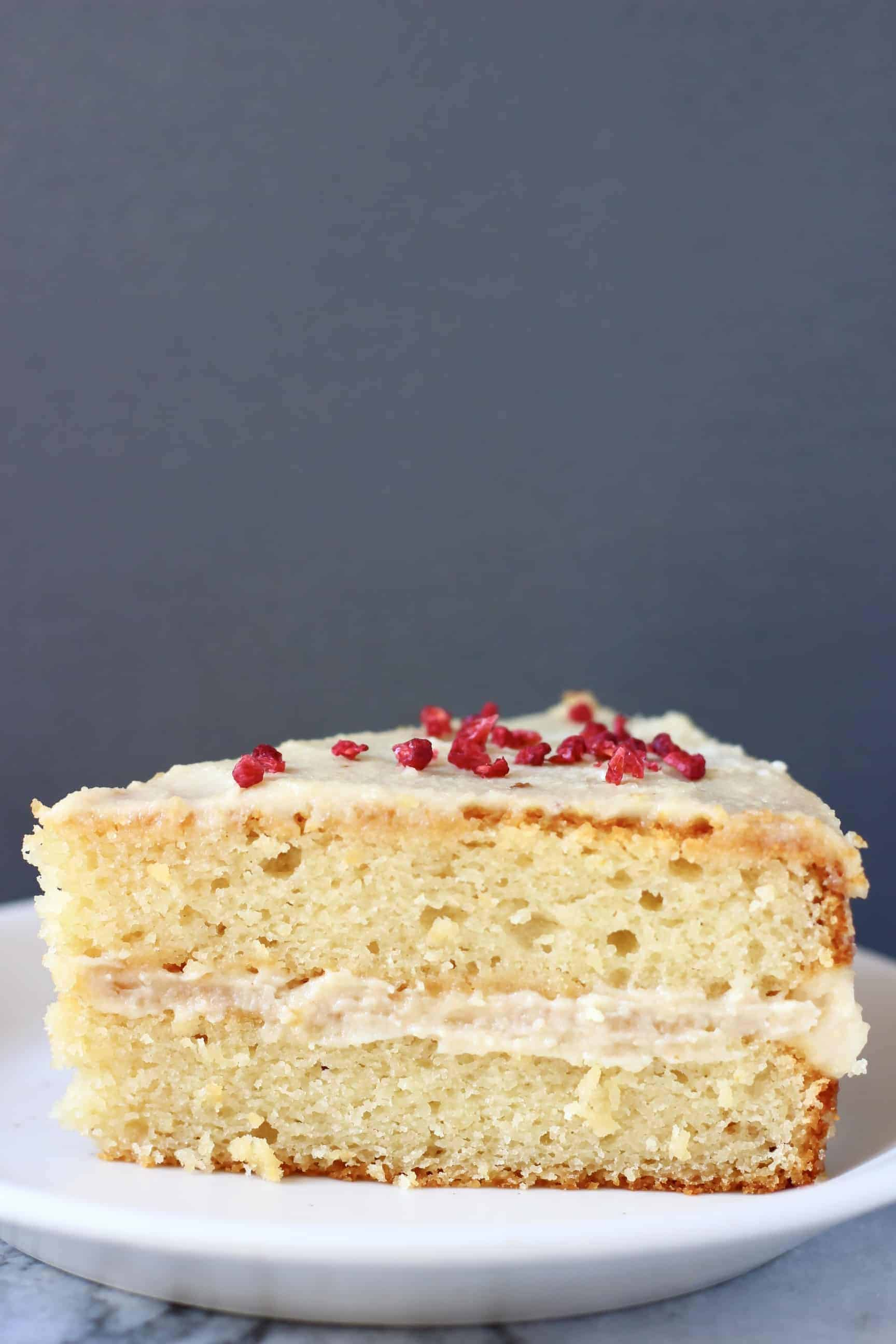 A slice of gluten-free vegan vanilla cake with white frosting on a plate