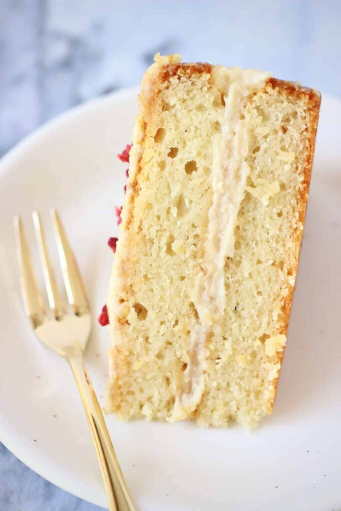 A slice of vanilla sponge layer cake with white frosting on a plate with a gold fork