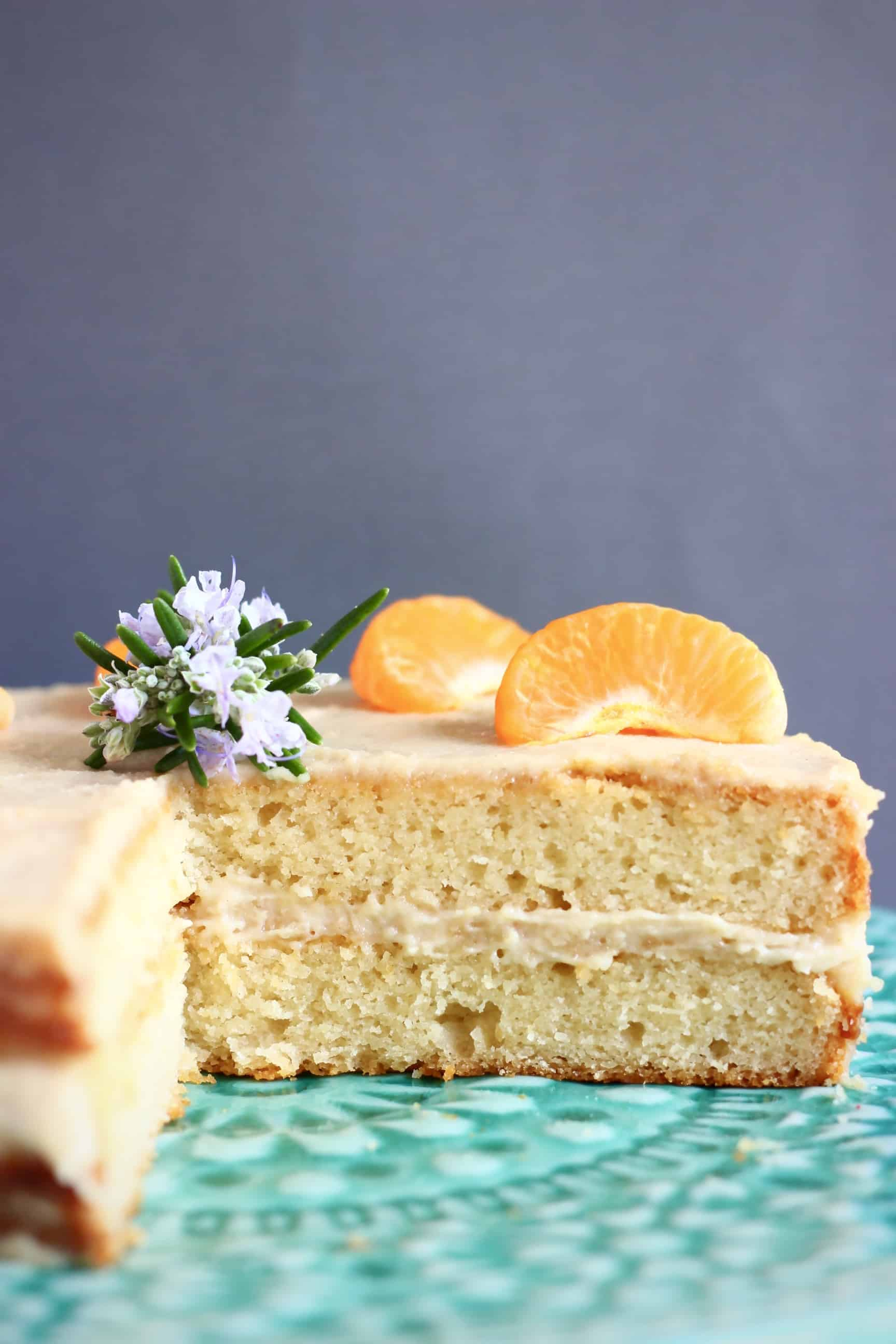 Sliced gluten-free vegan orange cake with buttercream topped with clementine segments