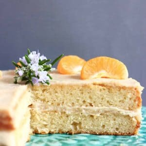 Sliced orange sponge layer cake with buttercream topped with clementine segments