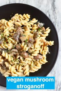 Fusili pasta with mushroom stroganoff sauce on a black plate against a marble background