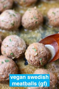 Brown meatballs in a brown gravy topped with green herbs with a wooden spoon lifting up one meatball