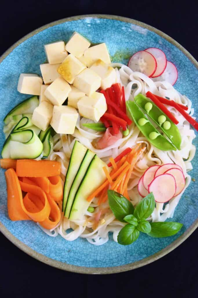 Rice noodles, tofu cubes and raw vegetables on a blue plate against a black background