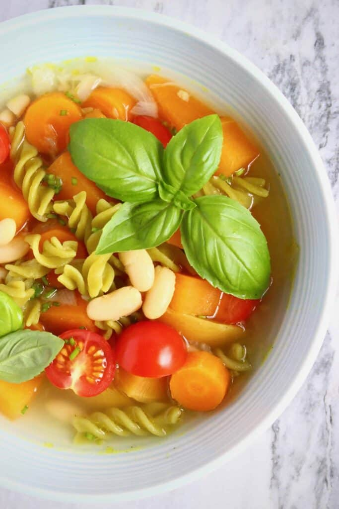Soup with green pea pasta, carrots, white beans, tomatoes and a sprig of basil in a light blue bowl against a marble background